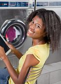 Portrait of young African American woman holding digital tablet sitting at laundromat