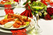 Lobster and white wine on a festive table with red folded napkins and red ribbon trims