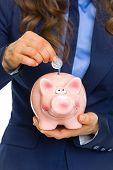 Closeup On Business Woman Putting Coin Into Piggy Bank