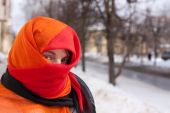 stock photo of yashmak  - young beautiful woman in red purdah against street - JPG
