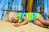 The Little Girl Fell Asleep On The Deck Of A Sailboat