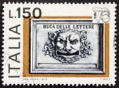ITALY - CIRCA 1976: a stamp printed in Italy celebrates Expo Italy showing image of an old postbox face shaped. Italy, circa 1976