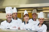 Five chefs posing with crossed arms smiling at the camera