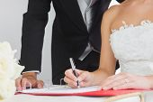 Close up of young bride signing wedding contract being watched by her husband