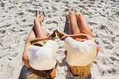 Sexy blonde and brunette on the beach wearing straw hat clinking their glass bottle