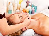 Young woman getting facial  massage in spa.