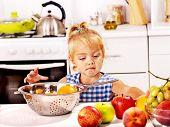 Child put fruit in colander at kitchen.