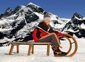 Girl on a sleigh,in the background Breithorn and Klein Matterhorn,Swiss Alps
