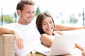 Couple in sofa with laptop pc computer at home laughing happy relaxing together having fun. Romantic young happy multiracial couple lying resting having fun together watching a movie. Man and woman.