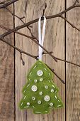 Christmas tree decoration hanging on a twig on against wooden background