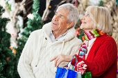 Happy senior couple with shopping bags looking up at Christmas store
