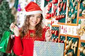 Portrait of happy young woman in Santa hat carrying shopping bags at store