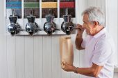 Side view of senior man buying coffee beans from vending machine at grocery store