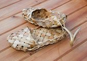 foto of baste  - Russian bast shoes standing on the wooden floor - JPG
