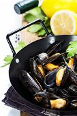 Mussels cooked with white wine sauce in a metal pot