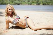 Young adult attractive beautiful blonde woman in bikini on the beach