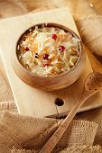 sauerkraut - Sour cabbage -  wooden bowl with bay leaves