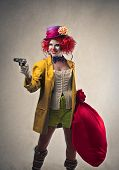 stock photo of delinquency  - beautiful robber clown with gun and big sack of money - JPG