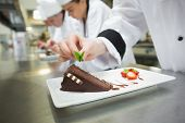 Close up of chef putting mint leaf on chocolate cake in busy kitchen