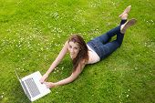 Happy young woman lying on a lawn using her laptop smiling at camera
