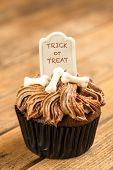 stock photo of tombstone  - Halloween cupcake with the wording of Trick or Treat on the tombstone cake topper close up - JPG