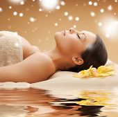 health and beauty concept - woman in spa salon lying on the massage desk