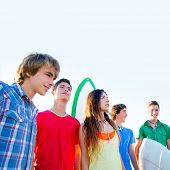 Teenager surfers boys and girls group happy in beach shore high key