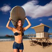 Brunette surfer teen girl holding surfboard in Huntington Beach California