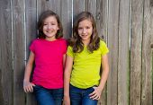 Twin sisters with different hairstyle posing on wood backyard fence