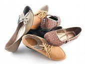 Pile of various female flat shoes isolated over white