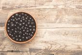picture of chokeberry  - Black chokeberry in brown bowl on wooden table - JPG