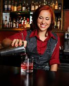 Beautiful redhead barmaid making cocktail