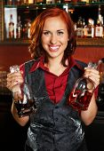 Beautiful redhead barmaid with bottles behind bar counter