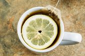 stock photo of hot-water-bag  - Horizontal closeup photo of tea bag and fresh lemon slice in cup of hot water on stone counter top - JPG