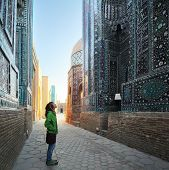 Young lady tourist enjoying oriental atmosphere of ancient complex of Shah i Zinda. Samarkand, Uzbek