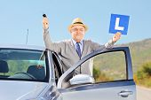 Smiling senior man posing next to his car holding a L sign and car key after having his driver's lic