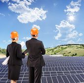 Team of architects examining solar panels under sunny sky, Macedonia, shot with a tilt and shift len