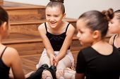 stock photo of leotard  - Happy little girl having fun with her friends during dance class in a dance academy - JPG