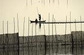 A Fisherman Silhouette Near U Bein's Bridge At Sunset.