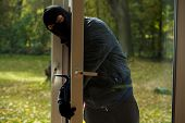 stock photo of sneak  - A masked burglar sneaking through the window - JPG