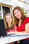 Mother and daughter working on a portable computer at home in the garden