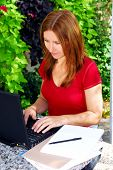 Mature woman working on portable computer in her garden at home