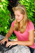 Teenage girl typing on a portable computer outside