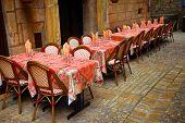 Outdoor restaurant patio on medieval street of Sarlat, Dordogne region, France