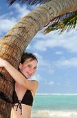 Happy young girl higging a palm tree on tropical beach