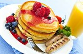 Breakfast of buttermilk pancakes with sausages and fresh berries