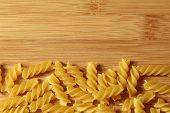 Uncooked Italian pasta noodles background on wooden texture