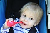 stock photo of teething baby  - Child Baby boy in stroller teething and biting a toy - JPG
