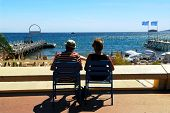 Couple relaxing in chairs on Croisette promenade in Cannes, France
