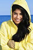 Portrait of beautiful smiling brunette girl wearing yellow raincoat